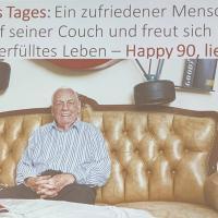 Ein zufriedener Mensch sitzt lächelnd auf seiner Couch und freut sich über sein langes und erfülltes Leben – Happy 90, lieber Kurt!